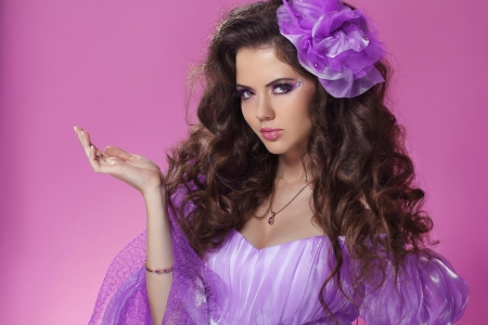 Beautiful woman with long curly hair style over purple photo