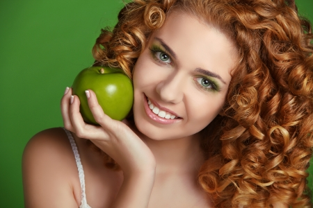 Young happy smiling beautiful woman with apple. Curly hair Stock Photo - 16960625
