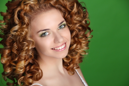 Curly Hair. Attractive smiling woman portrait on green background. Beauty Portrait. Stock Photo - 16960614