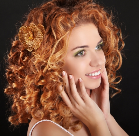 Attractive smiling girl with golden Curly Hair on dark background. Beauty Portrait. Stock Photo - 16982178
