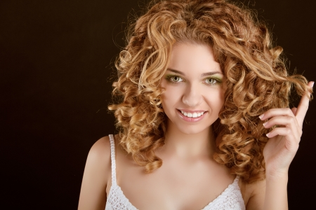 Attractive smiling teen girl with Curly Hair wavy hair, curl on finger Stock Photo - 16960615