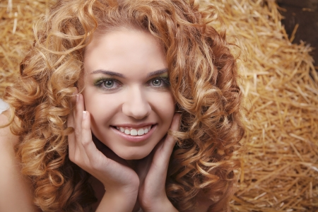 Beautiful smiling woman portrait with long curly hairs on haystack, harvest background Stock Photo - 16960627