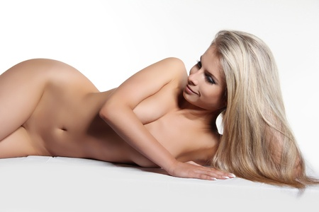 naked female body: Healthy woman with long glossy hair lying over white Stock Photo