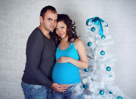 Loving couple family embracing with pregnant belly and Christmas gift box  photo