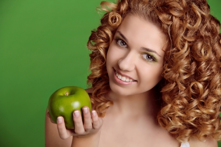 Portrait of Caucasian young woman with apple. over green photo