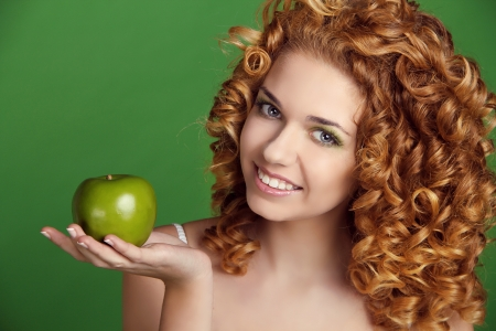 Attractive smiling woman portrait with long glossy hair holding apple over green Stock Photo - 17260664