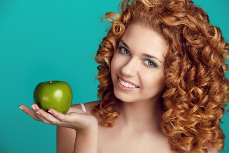 Beautiful smiling woman portrait with long glossy hair eating apple over blue photo