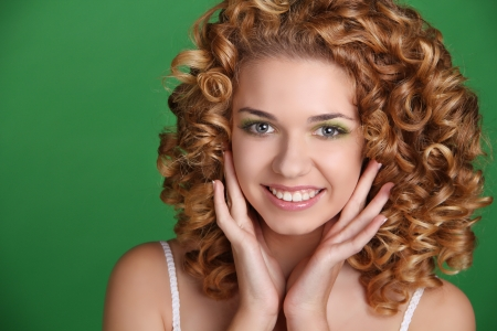 Attractive smiling woman portrait with long glossy hair over green Stock Photo - 17314482