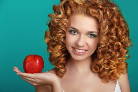 Young happy smiling beautiful woman with apple, carefree healthy hair photo