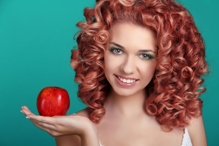 Portrait of young beautiful woman with coloring glossy hair holding red apple photo