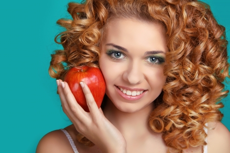 Attractive happy smiling woman with healthy glossy hair holding red apple Stock Photo - 17260655