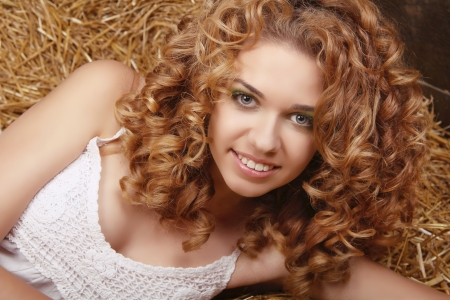 Happy smiling woman portrait with healthy curly hairs on natural harvest background photo