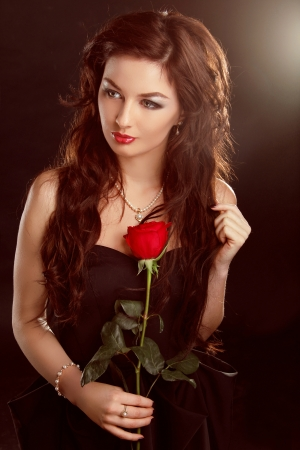 Portrait of beautiful brunette woman with red rose photo