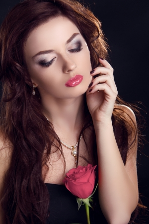 Beautiful brunette woman with rose flower. Glamour portrait of female makeup photo