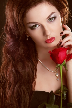 Beautiful brunette woman with red rose and long curly hair photo