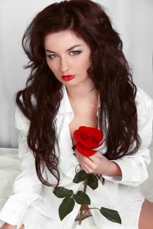 Sexy woman with red rose wearing in shirt on white bed photo