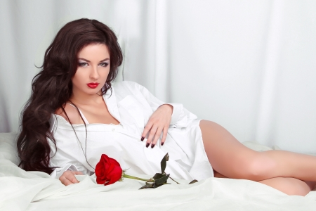 Beautiful woman with red rose posing in shirt lying on the white bed photo