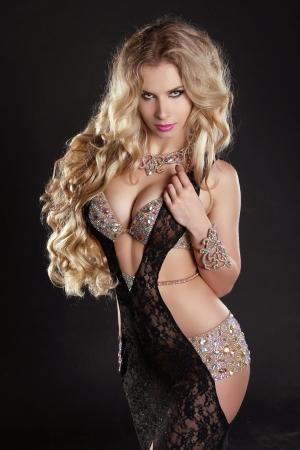 Slim beautiful woman with long hair wearing luxurious dress over dark Stock Photo - 17260660