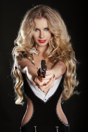 Sexy blond woman shooting gun isolated on black background photo