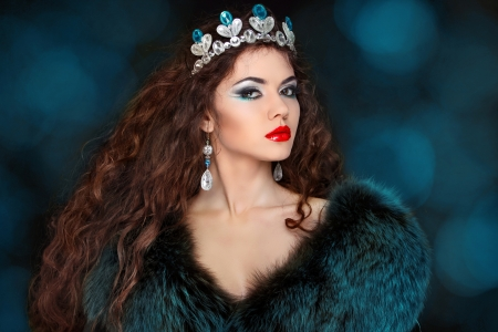 Beautiful woman with long hair in fur coat. Jewelry and Beauty.  photo