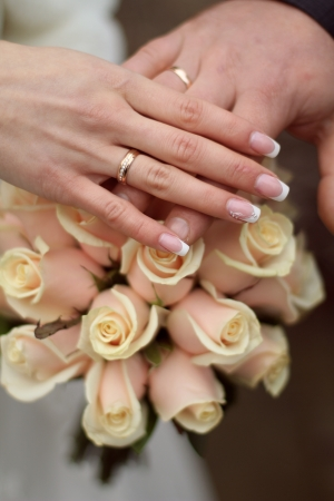 Wedding rings and Hands on wedding bouquet photo