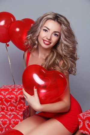 Valentines Day. Beautiful happy woman with red heart balloons on gray background. photo