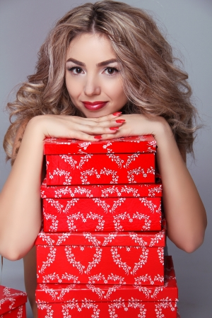 Beautiful attractive woman with red gift box on gray background photo