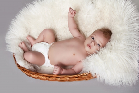 Cute adorable baby lying and smiling on grey background photo