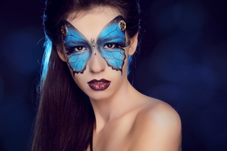 Fashion woman Portrait. Butterfly makeup,  face art make up photo