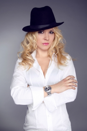 wristwatch: Woman wearing in white shirt and black hat isolated on grey background
