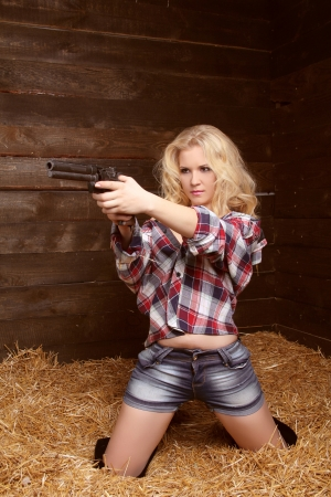 Danger sexy woman with revolver over pile of straw texture background Stock Photo