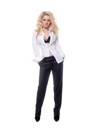 black pants: Full length portrait of a stylish young woman in Men style standing with hands in pockets over white background