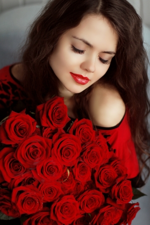 Portrait of attractive Caucasian smiling woman with red roses bouquet flowers  photo