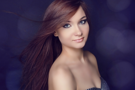 Young beautiful woman with long brown magnificent hair.  Closeup portrait of fashion model posing at studio. photo