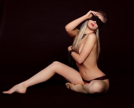 artistic nude: Erotic lady. Sexy woman in black lingerie over black background.