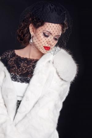 bontjas: Elegante vrouw draagt in witte bontjas geïsoleerd op zwarte achtergrond