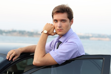caucasian appearance: Handsome Man casually leaning against the car, outdoor portrait  Stock Photo