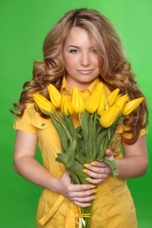 Beautiful Girl With Tulip Flowers over green background. Beauty Model Woman Face. photo