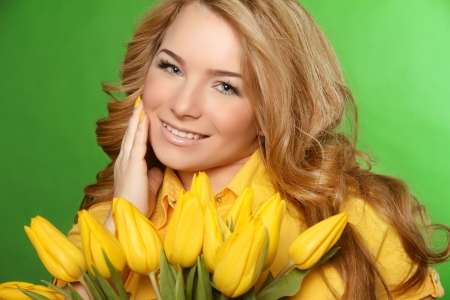 Happy smiling girl with spring-flowering yellow tulips isolated on green background photo