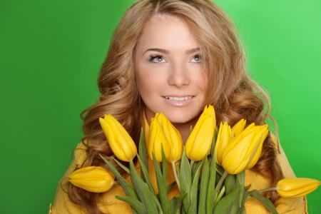 Happy smiling girl with spring-flower yellow tulips isolated on green background photo