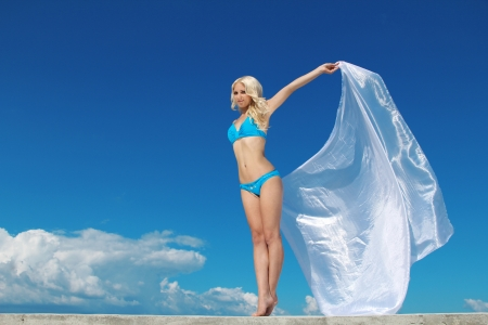 Beautiful woman with scarf over blue sky, Free lady on vocation. Travel and Vacation. Freedom Concept photo