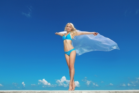 Portrait of young woman feeling free against blue sky with blowing fabric. Freedom Concept photo