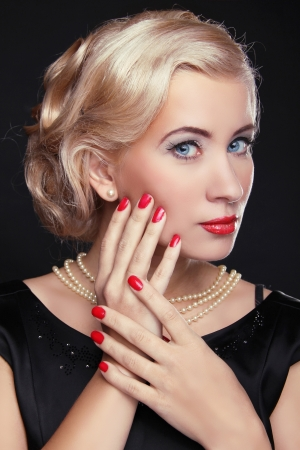 Blond woman with make up and red manicured nails over black, studio photo photo