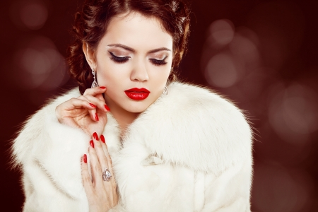 Fashion woman with red lips and nails in fur coat. Luxury and  Jewelry Stock Photo