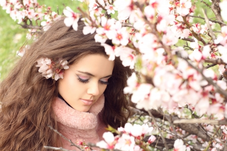 shy woman: Beauty woman, outdoors portrait of teen girl beautiful cheerful enjoying with long brown hair over pink blossom background
