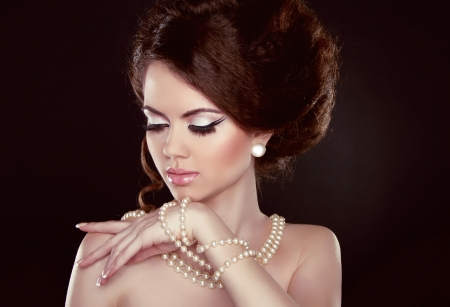 pearl necklace: Beautiful pretty woman with pearls on her neck isolated on dark background