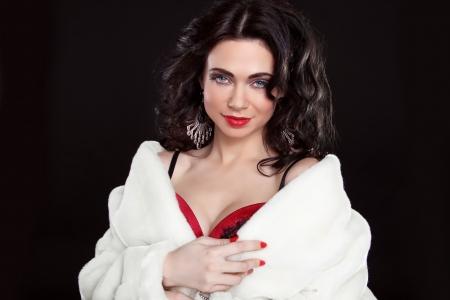 Brunette beautiful girl posing in fur coat over dark Stock Photo - 18665388