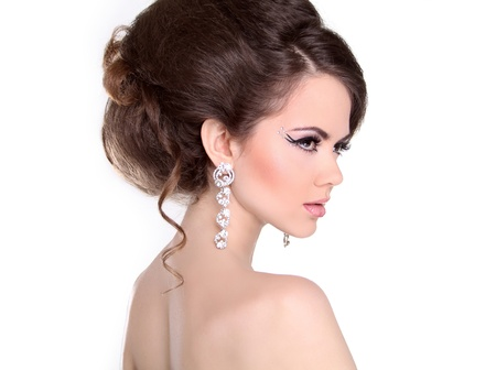 Hair style. Beautiful Brunette Girl with hairstyle and make up isolated on white background. Jewelry and Fashion.
