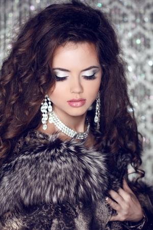 Beautiful woman with long brown hair in luxury fur coat. Closeup portrait of a fashion model posing at studio. photo