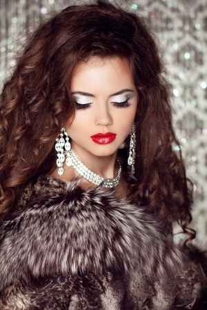 Fashion lady, Beautiful woman in fur coat posing in luxury brilliant jewelry at royal apartment interior. photo